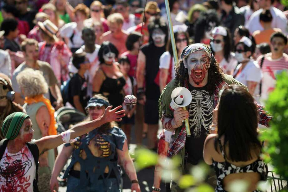 Daywalkers react to photographers during the fifth annual Red, White and Dead Zombie Walk Saturday, July 6, 2013, around the Seattle Center in Seattle. This year, the horde relocated from their long-time Fremont location to the larger Seattle Center to accommodate more roaming, undead bodies. Photo: JORDAN STEAD, SEATTLEPI.COM / SEATTLEPI.COM