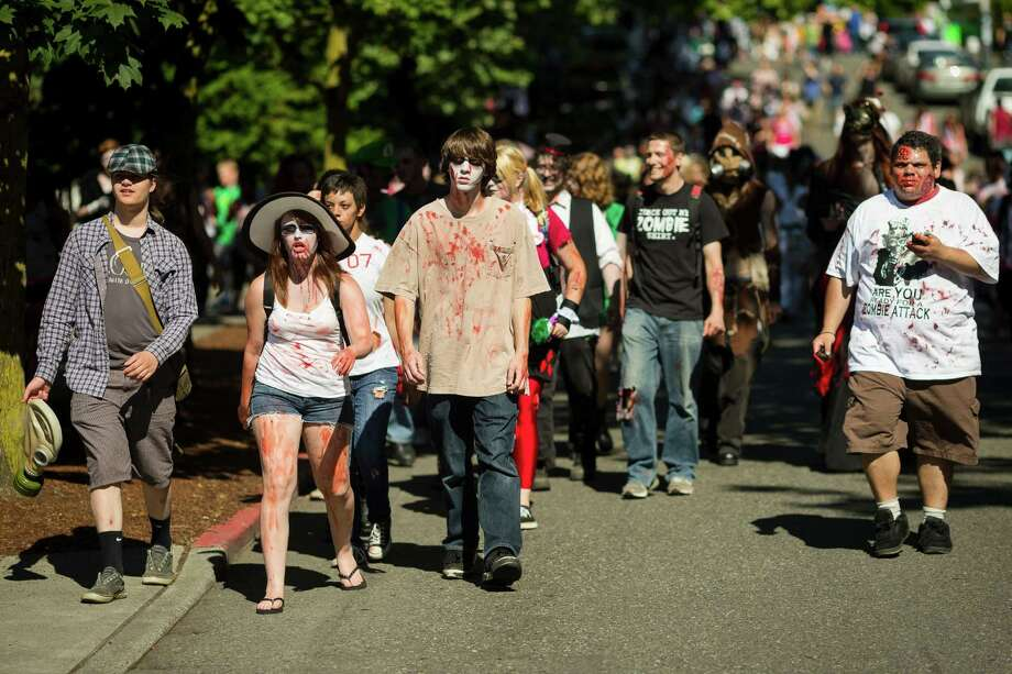 A mass of walkers approach Key Arena during the fifth annual Red, White and Dead Zombie Walk Saturday, July 6, 2013, around the Seattle Center in Seattle. This year, the horde relocated from their long-time Fremont location to the larger Seattle Center to accommodate more roaming, undead bodies. Photo: JORDAN STEAD, SEATTLEPI.COM / SEATTLEPI.COM