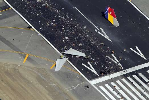 The debris of the tail section of the  fuselage of Asiana Airlines Flight 214 is visible on the runway at San Francisco International Airport after it crashed on landing and burned on Saturday, July 6, 2013. Photo: Carlos Avila Gonzalez, The Chronicle