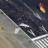 The debris of the tail section of the  fuselage of Asiana Airlines Flight 214 is visible on the runway at San Francisco International Airport after it crashed on landing and burned on Saturday, July 6, 2013.
