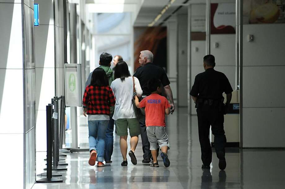A family of passengers from Asiana Airlines Boeing 777 which crashed while it was attempting to land at San Francisco International Airport are escorted out of the Reflection Room in San Francisco International Airport where flight passengers are being held on July 6, 2013. Photo: Michael Short, Special To The Chronicle