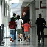 A family of passengers from Asiana Airlines Boeing 777 which crashed while it was attempting to land at San Francisco International Airport are escorted out of the Reflection Room in San Francisco International Airport where flight passengers are being held on July 6, 2013.