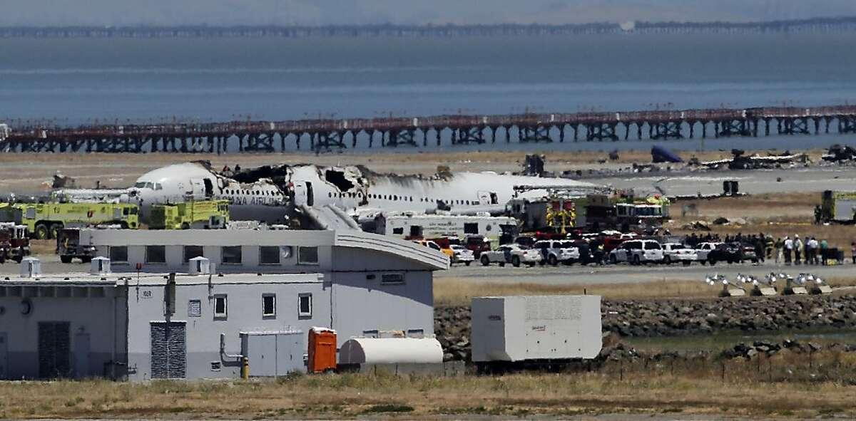 The wreckage of Asiana flight 214 sits beside the runway in San Francisco, Calif., on Saturday July 6, 2013, following a crash landing this morning at San Francisco International airport.