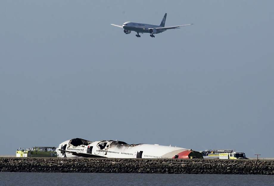 An Eva Air jetliner comes in for a landing above the Asiana Airlines Boeing 777 that crashed while attempting to land from Seoul, South Korea, at San Francisco International Airport in San Francisco, Calif. on Saturday, July 6, 2013. Photo: Paul Chinn, The Chronicle