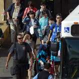 Emergency personnel assist passengers to transportation at the International terminal in San Francisco, Calif., on Saturday July 6, 2013, following the earlier crash of Asiana Airlines flight 214 at SFO.