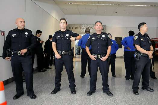 SFPD officers stand guard in front of the Reflection Room, where potential victims of the Asiana plane crash and their families are being held in the North Wing of the International Terminal at SFO in San Francisco, CA Saturday, July 6th, 2013. Photo: Michael Short, Special To The Chronicle
