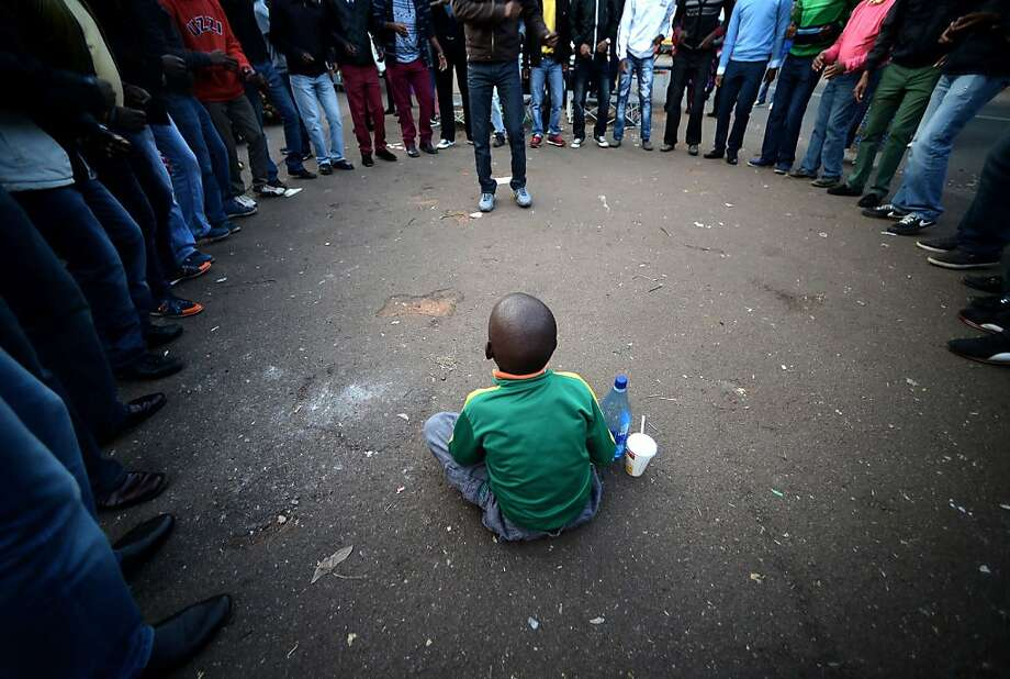 A child sits in the center of a gospel group singing outside of the Mediclinic Heart hospital in Pretoria on July 6, 2013 where former South African president Nelson Mandela lays in critical condition. Emotional crowds gathered outside the hospital, as relatives and clan elders made preparations for the revered former South African leader's final journey. Singing supporters amassed outside the Pretoria hospital where the 94-year-old anti-apartheid hero was fighting for his life. AFP PHOTO / Filippo MONTEFORTEFILIPPO MONTEFORTE/AFP/Getty Images Photo: Filippo Monteforte, AFP/Getty Images