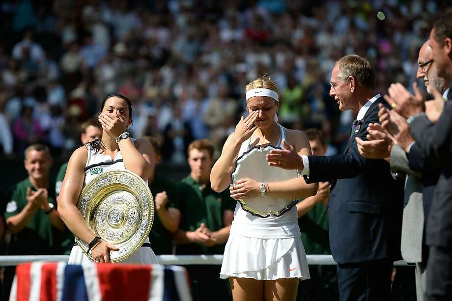 LONDON, ENGLAND - JULY 06:  Marion Bartoli of France and Sabine Lisicki of Germany react as they hold their trophies following the presentation ceremony after their Ladies' Singles final match on day twelve of the Wimbledon Lawn Tennis Championships at the All England Lawn Tennis and Croquet Club on July 6, 2013 in London, England.  (Photo by Dennis Grombkowski/Getty Images Photo: Dennis Grombkowski, Getty Images