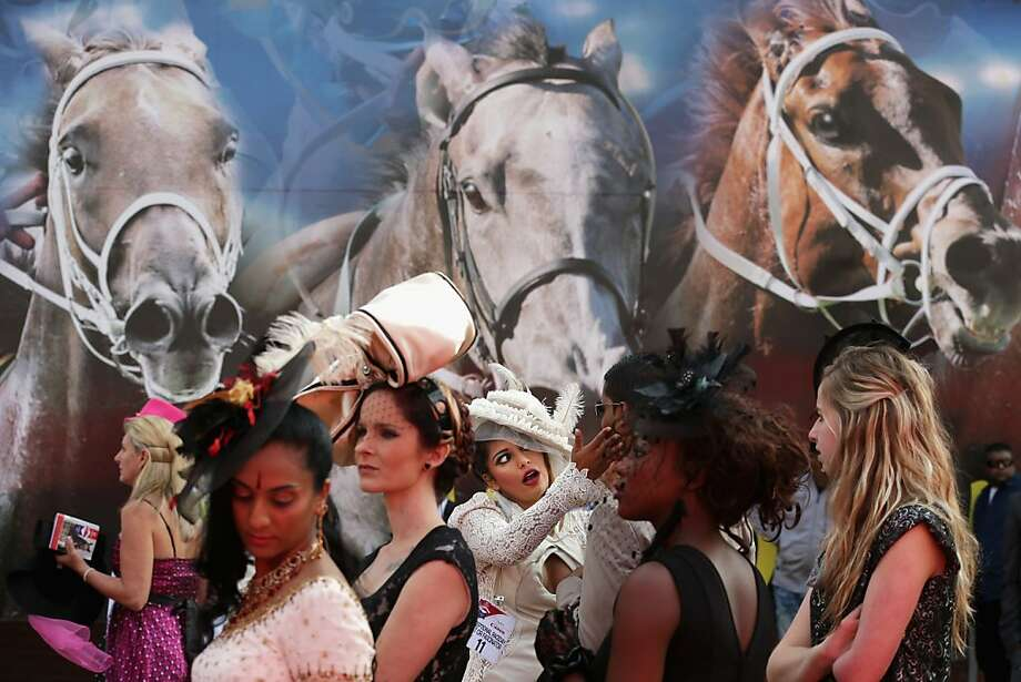 DURBAN, SOUTH AFRICA - JULY 06:  Racegoers participate in a fashion competition during the Durban July horse races July 6, 2013 in Durban, South Africa. South Africa's premier horse racing event, the 2200-meter Durban July is held annually on the first Saturday of July since 1897 and offers a purse of 2.5 million Rand or about US $245,000.  (Photo by Chip Somodevilla/Getty Images)  Photo: Chip Somodevilla, Getty Images