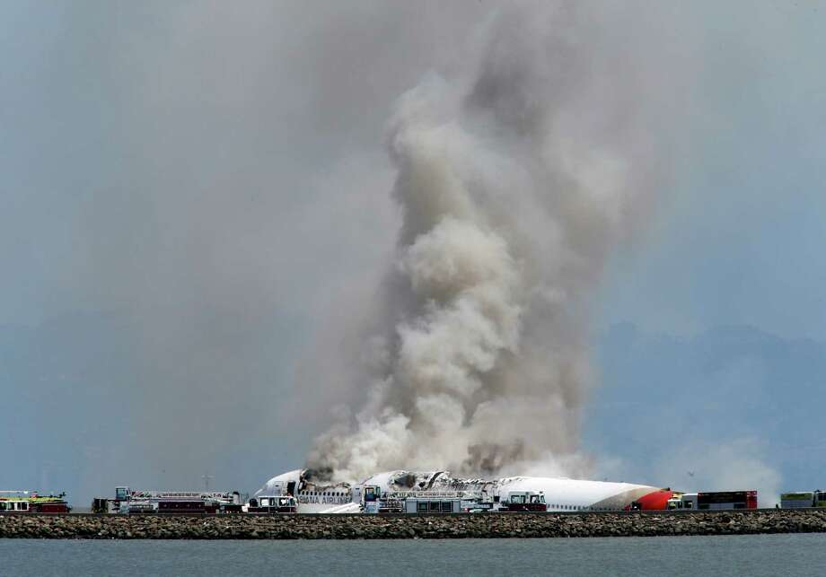 Smokes rises from Asiana Flight 214 after it crashed at San Francisco International Airport in San Francisco, Saturday, July 6, 2013. (AP Photo/Bay Area News Group, John Green) Photo: John Green, MBR / San Jose Mercury News