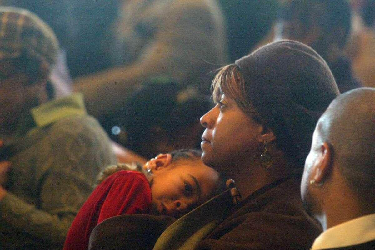 Mom, Anita Johnson cradles her daughter, Morgan, 3, during the MLK Service at St Paul Missionary Baptist Church. Monday, Jan. 18, 2010