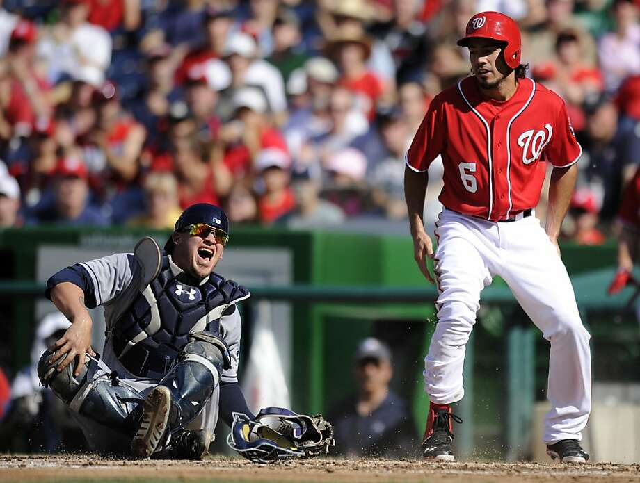 San Diego Padres catcher Yasmani Grandal, left, reacts after he was injured on a play at home as Washington Nationals' Anthony Rendon (6), who was out on the play, looks on during the third inning of a baseball game on Saturday, July 6, 2013, in Washington. The Nationals won 5-4. (AP Photo/Nick Wass) Photo: Nick Wass, Associated Press