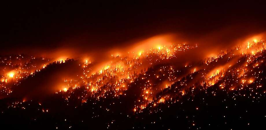 SPRING MOUNTAINS NRA, NV - JULY 06:  Smoke and flames from the Carpenter 1 fire are seen along a ridgeline in the Spring Mountains range early on July 6, 2013 in the Spring Mountains National Recreation Area, Nevada. More than 9,000 acres have burned since lightning sparked the blaze in Carpenter Canyon on the Pahrump, Nevada side of Mount Charleston on Monday. More than 400 firefighters are battling the as yet uncontained wildfire which crested the peak of Mount Charleston on Thursday, prompting the evacuation of 520 people as it began descending the east side of the mountain, about 35 miles northwest of Las Vegas.  (Photo by Ethan Miller/Getty Images) Photo: Ethan Miller, Getty Images