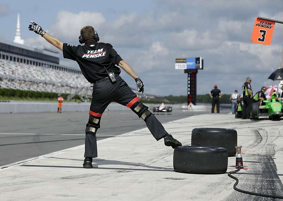 A crew member signals Helio Castroneves during a practice session for Sunday's Pocono IndyCar 400 auto race, Saturday, July 6, 2013, in Long Pond, Pa. (AP Photo/Mel Evans) Photo: Mel Evans, Associated Press