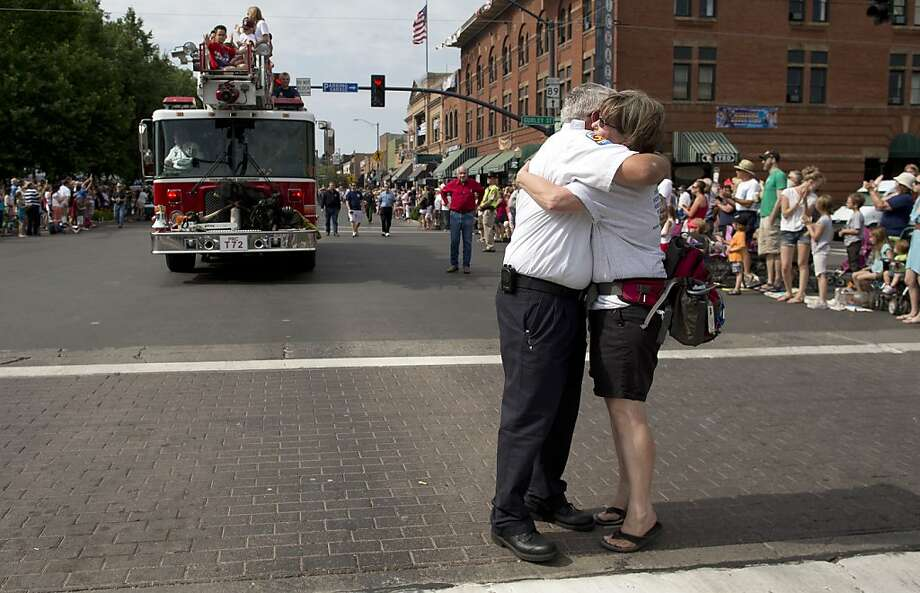 Prescott Fire Marshall Don Devendorf, left, stops to hug long-time friend Laura Halter while walking in the Prescott Frontier Days Rodeo Parade, Saturday, July 6, 2013 in Prescott, Ariz. Devendorf walked ahead of a Prescott Fire Department engine carrying family members of the 19 Granite Mountain Hotshot firefighters who were killed last week fighting a fire near Yarnell, Ariz. (AP Photo/Julie Jacobson) Photo: Julie Jacobson, Associated Press