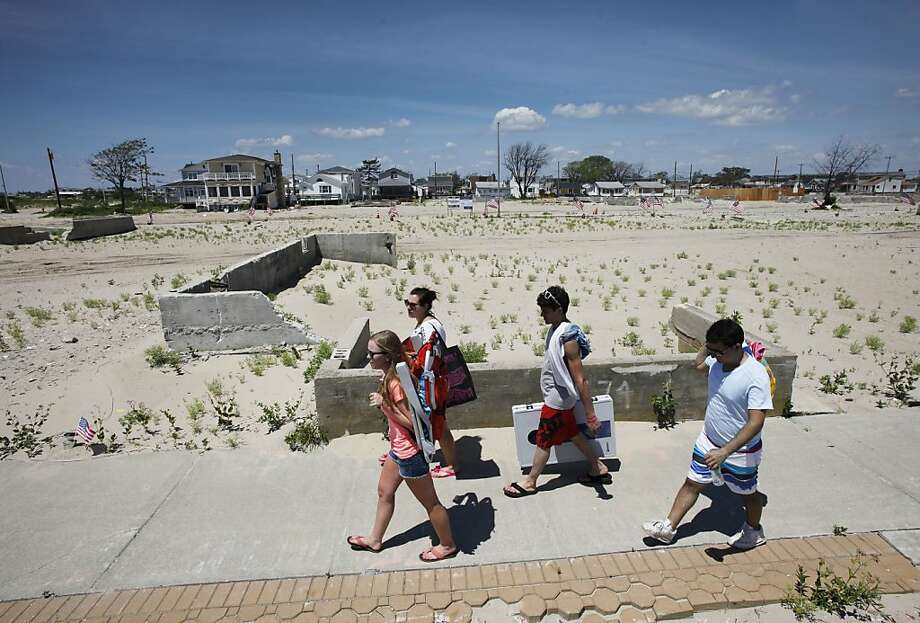 People walk to the beach in the Breezy Point section of the Queens borough of New York, Saturday, July 6, 2013, past the cleared site where 111 homes burned to the ground during Superstorm Sandy the night of Oct. 29, 2012. (AP Photo/Mark Lennihan) Photo: Mark Lennihan, Associated Press