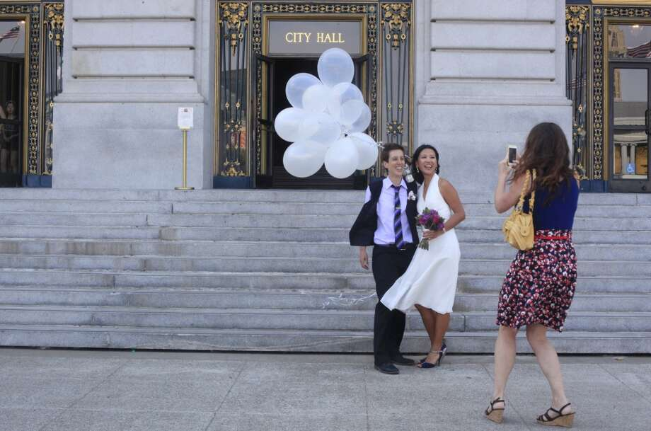 Lisas Dazols, 34, and Jenni Chang, 31, stop for a final photograph outside San Francisco City Hall after getting officially married on Tuesday July 2, 2013.