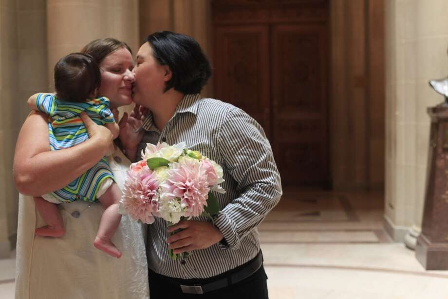 Moments after getting married while holding their son Jiso Seo, 5-months-old, Rosa Seo Reinikainen and A.J. Seo kiss at San Francisco City Hall on Tuesday July 2, 2013.