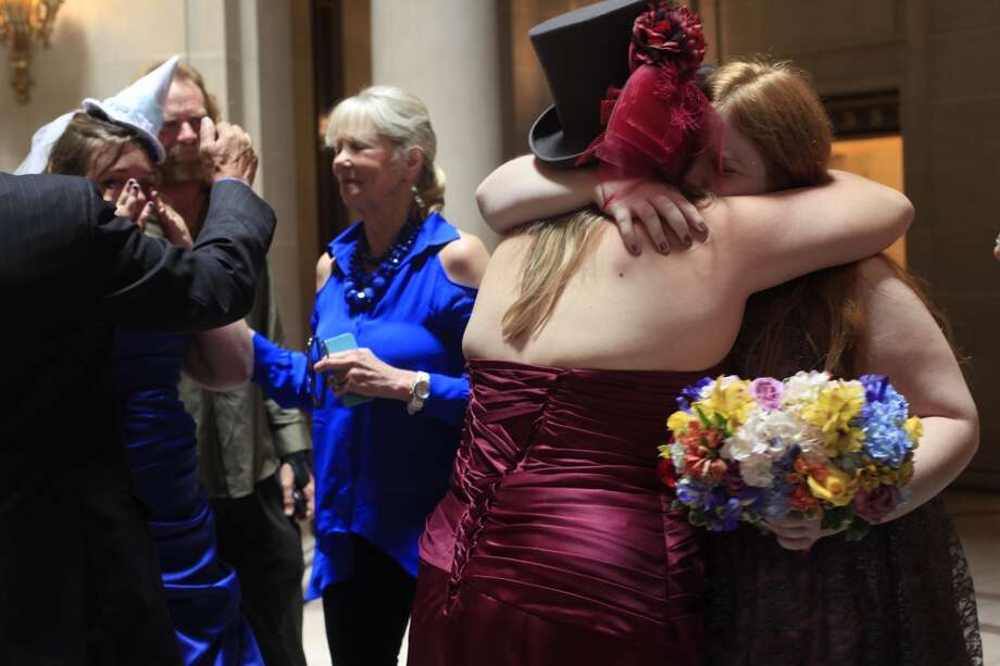 Moments after getting married, Melody and Anna Hennigh embrace their family members in San Francisco City Hall on Wednesday July 3, 2013.