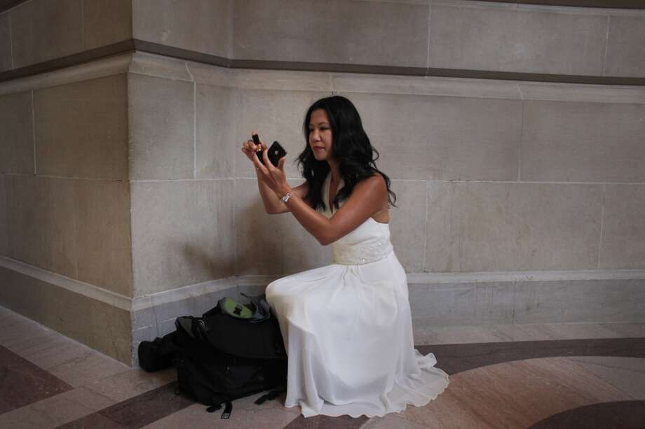 Before getting married at San Francisco City Hall, Jenni Chang checks her makeup under the rotunda on Tuesday July 2, 2013.