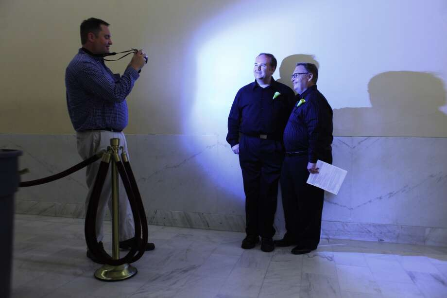 Graham Buffkin, 43, and Larry Swabe, 50, of Wake Forrest, North Carolina, pose for a photograph from their witness Jeff Shelby before getting married at San Francisco City Hall on Wednesday July 3, 2013.