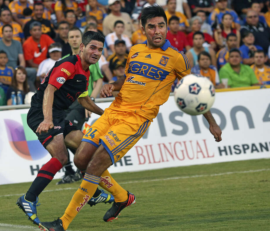 The Scorpions' Javier Saavedra (left) squeezes a shot past Tigres' Jose Arturo Rivas before 8,255 fans at Toyota Field. Photo: Tom Reel / San Antonio Express-News