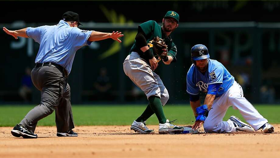 KANSAS CITY, MO - JULY 06:  Alex Gordon #4 of the Kansas City Royals is called safe by umpire Eric Cooper #56 as Eric Sogard #28 of the Oakland Athletics is late applying the tag during the game at Kauffman Stadium on July 6, 2013 in Kansas City, Missouri.  (Photo by Jamie Squire/Getty Images) Photo: Jamie Squire, Getty Images