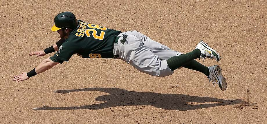 Oakland Athletics' Eric Sogard dives to third trying to reach on a fly ball hit by Coco Crisp during the seventh inning of a baseball game Saturday, July 6, 2013, in Kansas City, Mo. Sogard was out at third for the second out of the double play. (AP Photo/Charlie Riedel) Photo: Charlie Riedel, Associated Press