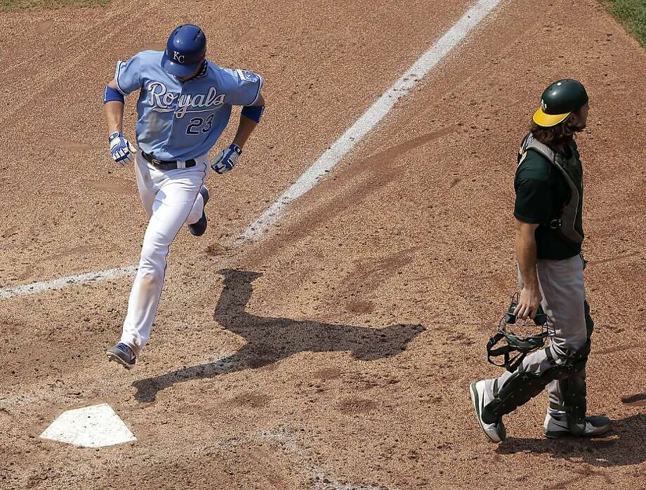Kansas City Royals' Elliot Johnson runs past Oakland Athletics catcher John Jaso to score on a sacrifice fly by Eric Hosmer during the seventh inning of a baseball game Saturday, July 6, 2013, in Kansas City, Mo. (AP Photo/Charlie Riedel) Photo: Charlie Riedel, Associated Press