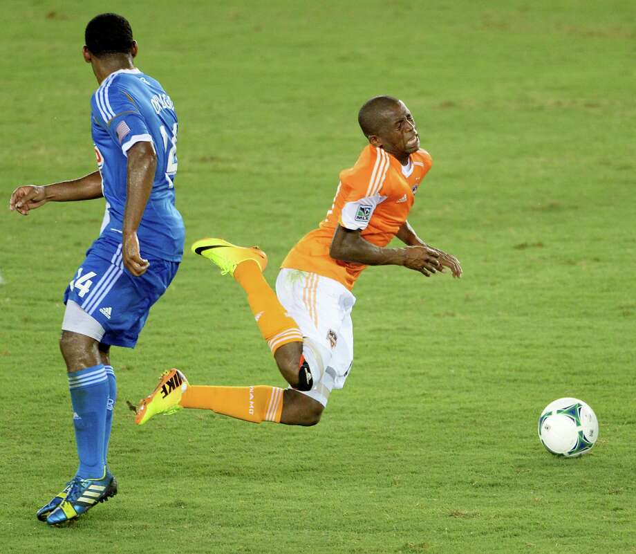 Houston Dynamo midfielder Boniek Garcia (27) takes a tumble as he is tripped up by Philadelphia Union midfielder Amobi Okugo (14) during the second half. Photo: Smiley N. Pool, Houston Chronicle / © 2013  Houston Chronicle