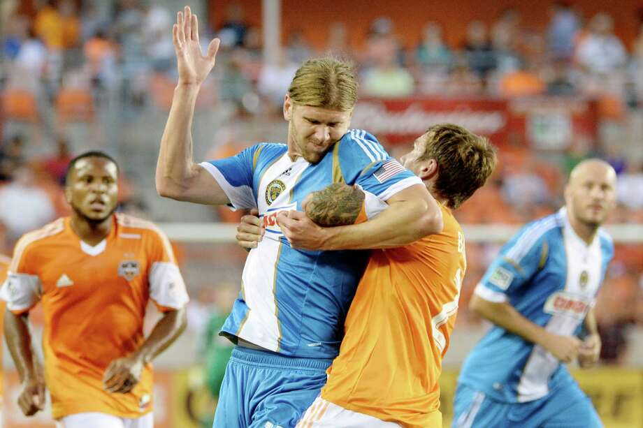 Houston Dynamo defender Eric Brunner (2) gets tangled with Philadelphia Union forward Aaron Wheeler. Photo: Smiley N. Pool, Houston Chronicle / © 2013  Houston Chronicle