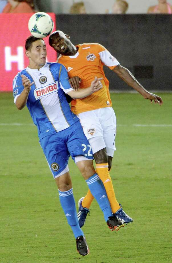 Houston Dynamo forward Omar Cummings (7) goes against Philadelphia Union midfielder Leo Fernandes (22) for a header. Photo: Smiley N. Pool, Houston Chronicle / © 2013  Houston Chronicle