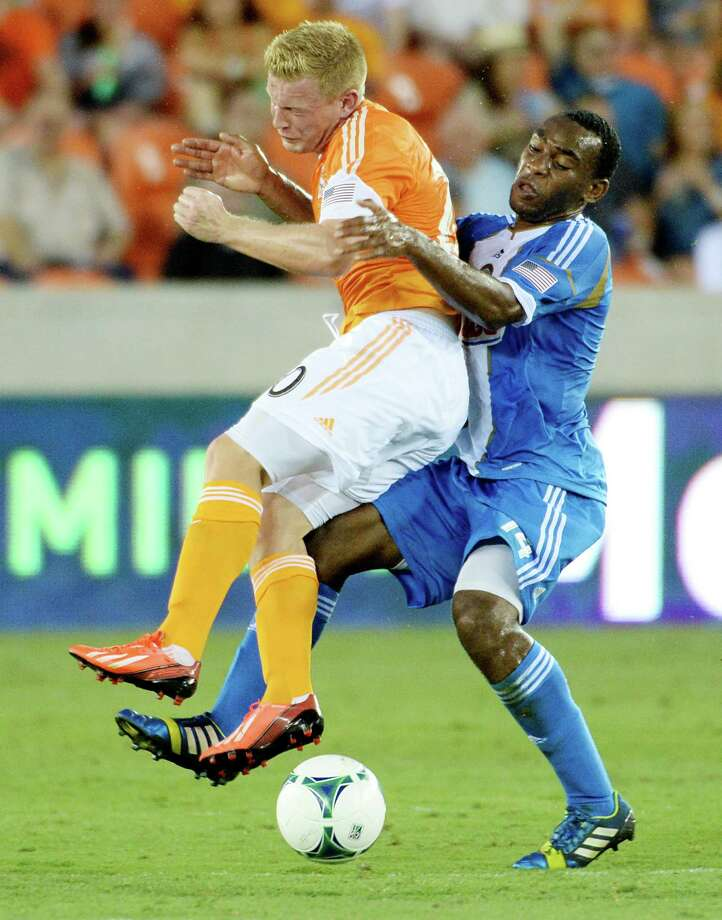 Philadelphia Union midfielder Amobi Okugo (14) collides with Houston Dynamo midfielder Andrew Driver (20) during the first half. Photo: Smiley N. Pool, Houston Chronicle / © 2013  Houston Chronicle