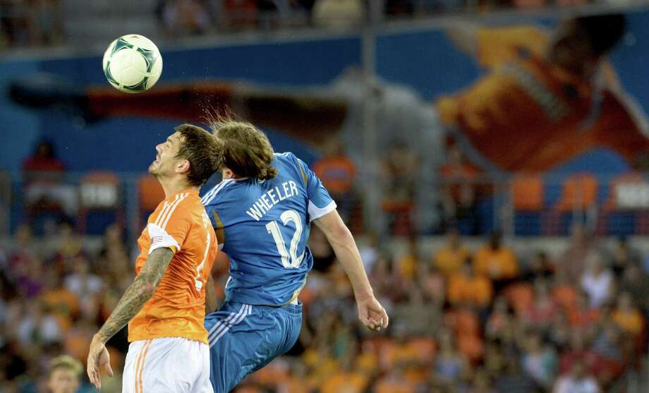 Houston Dynamo defender Eric Brunner (2) goes up for a header against Philadelphia Union forward Aaron Wheeler (12). Photo: Smiley N. Pool, Houston Chronicle / © 2013  Houston Chronicle