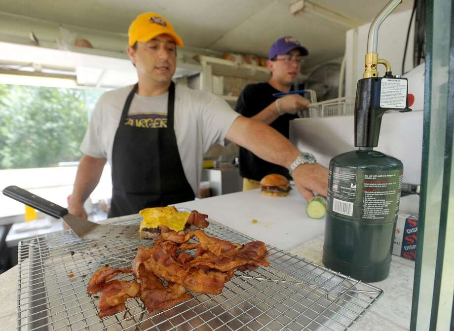 Jake Mazzu, left, and Nate Luna work in the Burger Guys food truck kitchen on Thursday. The food truck can be found in the King Arthur's Pub parking lot from 11 a.m. to 3 p.m. Tuesday through Friday and at Lunch at the Lake on Monday. Photo taken Thursday, June 20, 2013 Guiseppe Barranco/The Enterprise