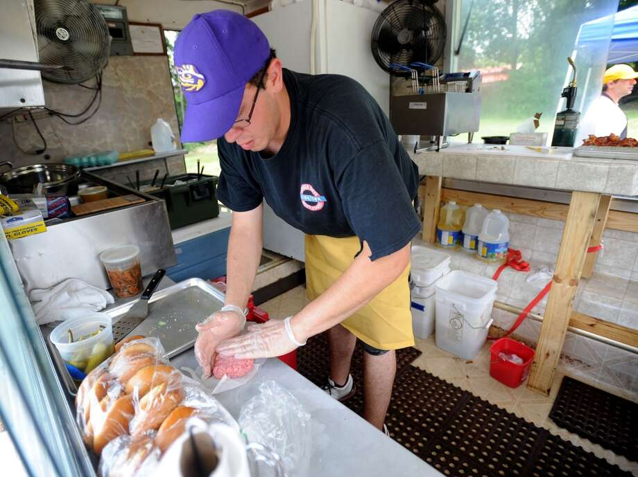 Nate Luna works in the Burger Guys food truck kitchen on Thursday. The food truck can be found in the King Arthur's Pub parking lot from 11 a.m. to 3 p.m. Tuesday through Friday and at Lunch at the Lake on Monday. Photo taken Thursday, June 20, 2013 Guiseppe Barranco/The Enterprise