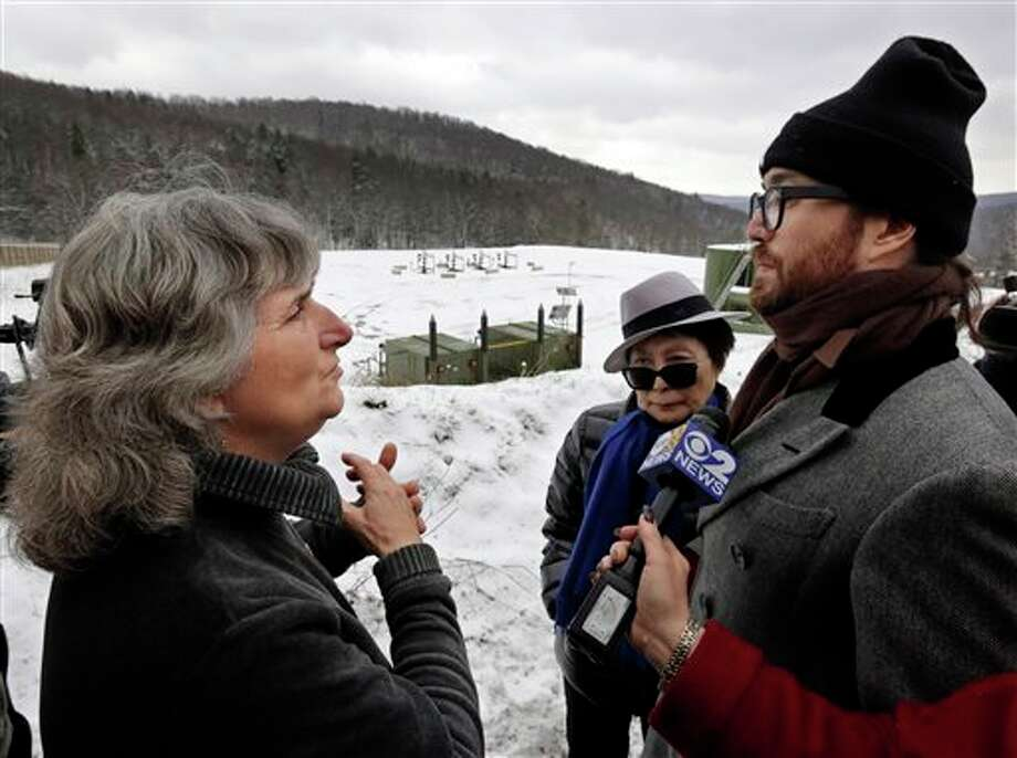 In this Jan. 17, 2013 photo, anti-fracking activist Vera Scroggins, left, talks with Yoko Ono, center, and Sean Lennon at a fracking site in Franklin Forks, Pa., during a bus tour organized by Scroggins. Scroggins, a scrappy, in-your-face videographer, is a self-appointed guide to the gas patch of northeastern Pennsylvania, where she lives in a single-wide trailer near a lake. Photo: Richard Drew, AP / AP