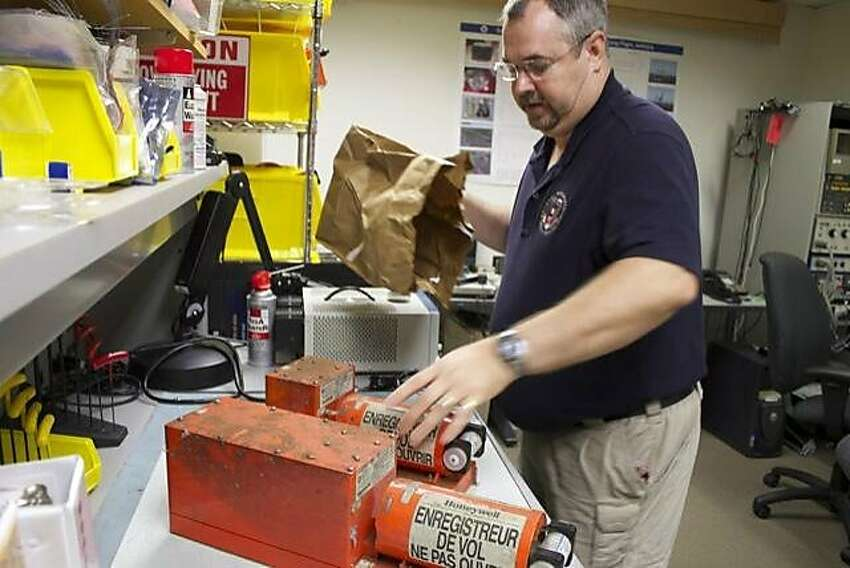 NTSB's Greg Smith with flight data recorder and cockpit voice recorder from Asiana 777 in NTSB's DC lab.