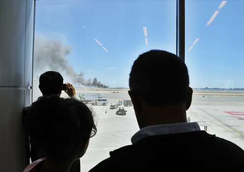 Travelers at San Francisco International Airport watch from their terminal as smoke rises from the crash of Asiana Airlines Flight 214.