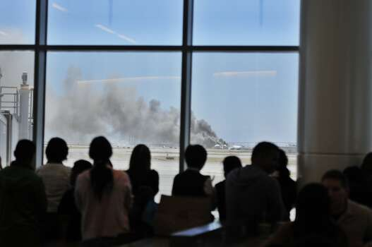 Travelers at San Francisco International Airport watch from their terminal as smoke rises from the crash of Asiana Airlines Flight 214. Photo: Kenan Chan