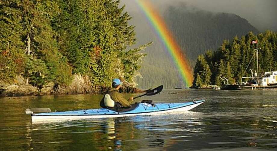 A kayaker paddles through calm waters near Tofino on Vancouver Island.