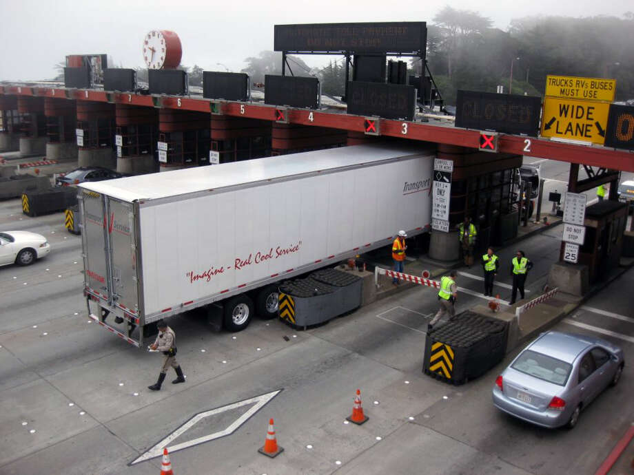 This photo provided by the Golden Gate Bridge, Highway and Transportation District shows a tractor-trailer that got stuck while trying to pass through the Golden Gate Bridge toll plaza Monday, July 1, 2013, in San Francisco. A a tow truck freed the truck after about 2 hours. Photo: AP