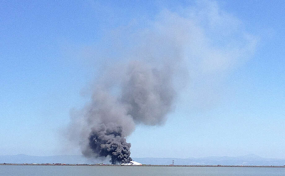 In this photo provided by Scott Sobczak, smoke rises from of Asiana Flight 214 after it crashed at San Francisco International Airport in San Francisco, Saturday, July 6, 2013. (AP Photo/Scott Sobczak) Photo: AP