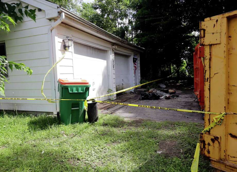 Police tape surrounds the former home of James and JoAnn Nichols, Wednesday, July 3, 2013, in Poughkeepsie, N.Y. James Nichols reported his wife missing on Dec. 21, 1985. He died of natural causes in December at the age of 82. A contractor cleaning out the debris-filled house in Poughkeepsie found JoAnn Nichols' skeleton Friday behind a false wall. Photo: AP