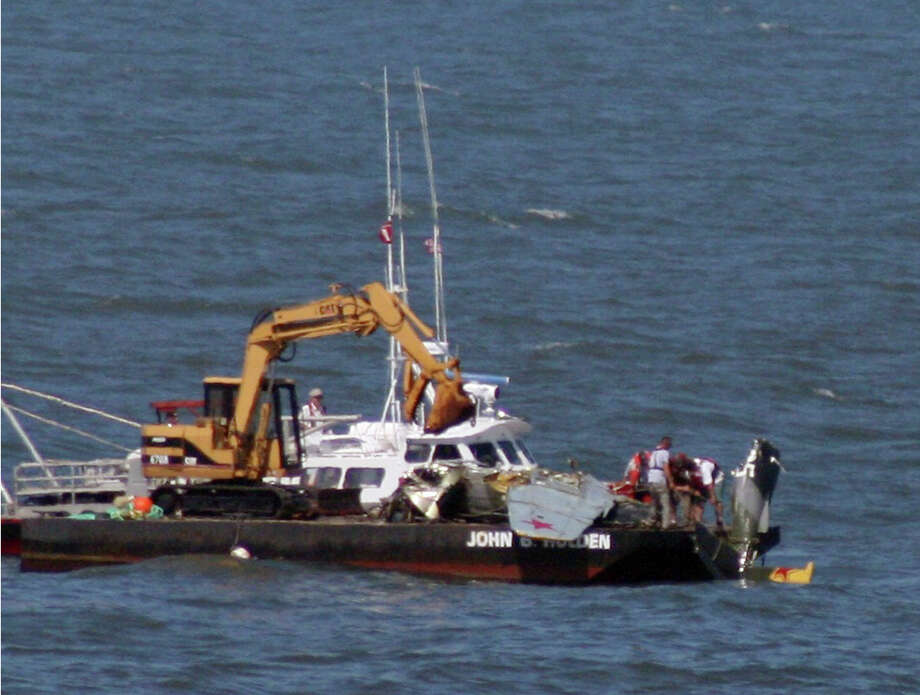 In this photo provided by Ed Tobias, a salvage crew inspects parts of a wing and the tail of a small plane, Thursday, July 4, 2013, that crashed Sunday near the beach at Ocean City, Md. The wreckage was recovered from about 30 feet of water Thursday. Photo: AP