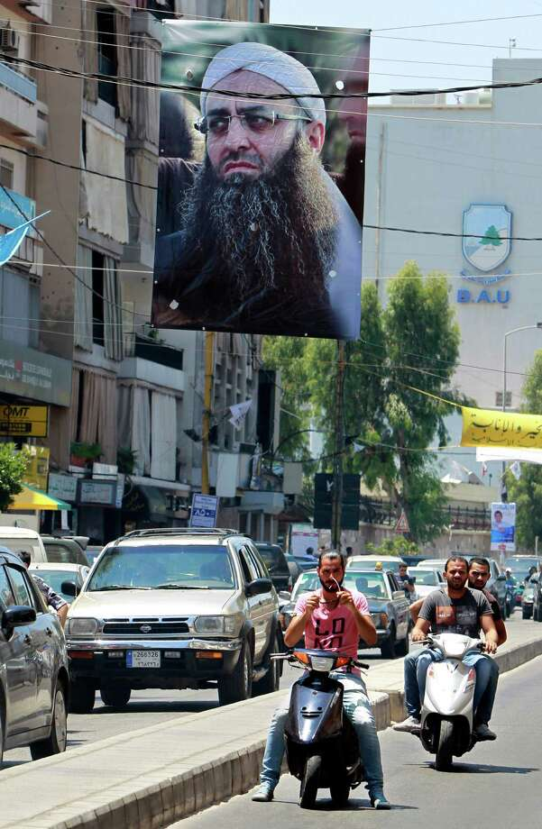 A poster of Lebanese hard-line Sunni cleric Sheik Ahmad al-Assir hangs on a street, in Beirut, Lebanon, Friday, July 5, 2013. On Thursday, al-Assir made an audio statement that he's survived the Lebanese army siege of his mosque in Sidon last week and called on his supporters to protest in the statement. Photo: AP
