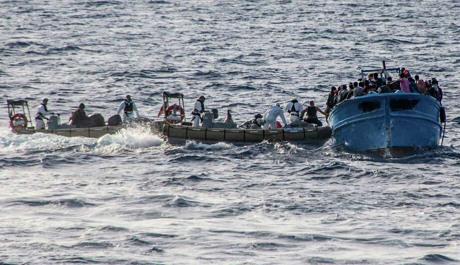 In this photo taken on July 2, 2013 and made available by the Italian Navy Wednesday, July 3, 2013, Coast Guard boats give help to a boat with some 80 migrants on a boat heading to Italy, in the Mediterranean sea, near the island of Lampedusa. The Vatican announced Monday that Pope Francis will go to Lampedusa island next week to meet with recently arrived migrants. Tens of thousands of clandestine migrants, many from Africa or the Mideast, head to Italian shores each year. Lampedusa is their frequent destination, closer to Africa than the Italian mainland. Photo: AP
