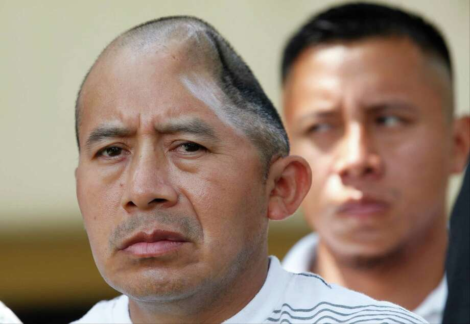 Antonio Lopez Chaj, left, a 43-year-old house painter, appears with his brother, Pedro Chang, right, at a news conference in Los Angeles Monday, July 1, 2013. Lopez Chaj is so badly brain damaged for a beating in a bar that left him with half his skull permanently bashed in that he cannot speak. His lawyers announced he has been awarded a $58 million by a jury in Torrance Superior Court. Photo: AP