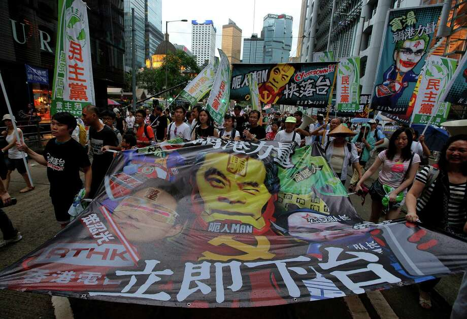 "Protesters carry a banner featuring with Hong Kong's Chief Executive Leung Chun-ying's picture and Chinese words ""Step down now"" in a downtown street during an annual pro-democracy protest in Hong Kong Monday, July 1, 2013. Tens of thousands of Hong Kong residents demanded their widely disliked Beijing-backed leader resign and pressing for promised democratic reforms so they can choose their own top representative. The march is an annual event that underscores the growing gulf between Hong Kong and the mainland 16 years after the city ceased to be a British colony and came back under Beijing's control. Photo: AP"