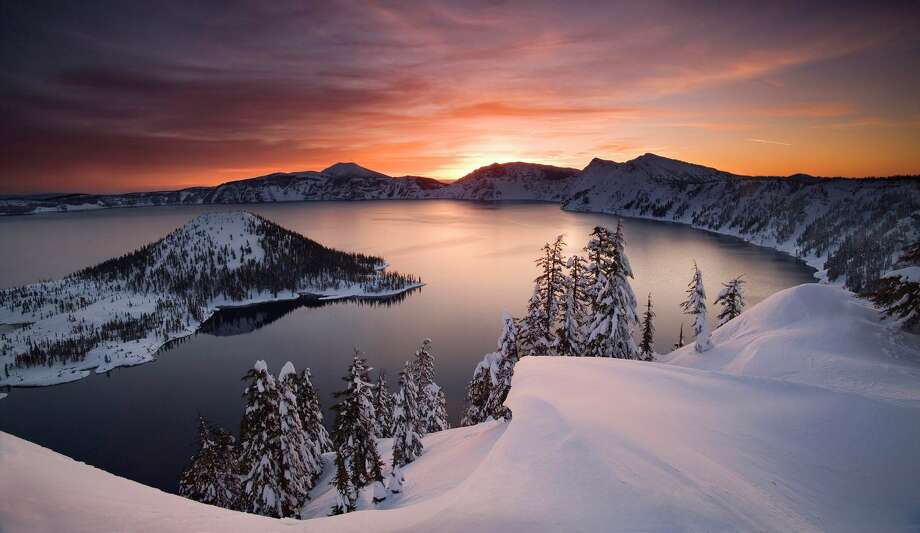 FILE - In this January 2006 file photo, the sun rises over Crater Lake, Ore.  Crater Lake National Park surrounds the deepest lake in the United States, and may soon have insufficient water supplies for its public operations.  State water regulations in the Klamath Basin have begun shutting off farmers' and ranchers' water for the first time, and could extend shutoffs to public lands including Crater Lake. Photo: AP